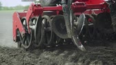 arando : Blades cultivator and seeder sowing machine working on agricultural field. Agricultural machinery for scattering seeds moving on farmer field