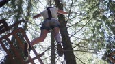 carbine : Young woman in protective equipment for climbing walking on rope on high in extreme park. Extreme sport for active people climbing trees in adventure park