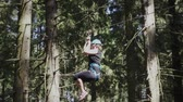 carbine : Young woman in protective helmet and belt moving on rope with carbine on high in extreme park. Extreme descend on rope between trees in climbing park Stock Footage