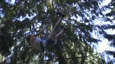 carbine : Young woman in safety equipment moving on rope with carbine on high in climbing park. Summer adventure climbing trees in extreme park outdoor Stock Footage