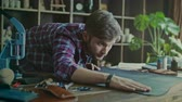 fabricante : Craftsman working with leather at home workshop. Work with love. Worker checking quality of leather material. Handsome man touching piece of leather lying on table at workshop Stock Footage