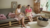 шерстяной : Two woman friends smiling and knitting wool clothes in home room. Woman hobby in cozy home