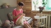 шерстяной : Young woman knitting wool sweater on couch in cozy room. Happy entrepreneur making handmade clothes at home workshop. Female lifestyle Стоковые видеозаписи