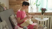шерстяной : Creative woman knitting wool sitting at couch in home. Talking woman knitting needles wool clothes in home workshop