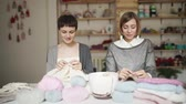 шерстяной : Two woman in knitted sweater smiling and enjoy hobby. Two woman friends together knitting wool clothes in workroom
