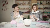 шерстяной : Two woman friends have fun knitting needles wool yarn in work studio. Knitting woman smiling and talking in workshop Стоковые видеозаписи