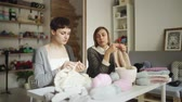 шерстяной : Two woman knitter making wool fabric sitting at table in textile workshop. Knitting woman working together in creative studio. Craft workshop Стоковые видеозаписи