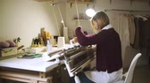 ткачество : Creative woman making knitted textile on loom machine in workshop. Young woman working on knitting machine. Manufacturing knitted fabric on weaving machine Стоковые видеозаписи