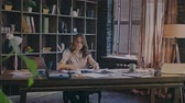 respectable : Responsible business woman working with documents in cozy dark office. Beautiful girl analysing market report. Business work at home. Attractive businesswoman working with papers at workplace Stock Footage