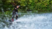 across : Handsome man wakesurfing in water splashes. Young man riding wakeboard on summer river. Waterskier moving fast in splashes. Wakeboarder surfing across river. Extreme lifestyle Stock Footage
