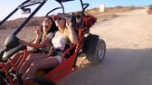 eğlenmek : Female rider have fun on desert buggy. Extreme girl driver enjoy desert travel. Women riding on sand buggy car. Woman showing peace hand