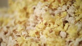 kernels : Ready popcorn falling in popcorn machine. Popcorn production process. Close up of process of pop corn production in slow motion. Cinema food background