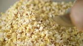 kernels : Pop corn background. Process of drying popcorn after manufacturing. Ready popcorn flakes in popcorn machine. Human hand pouring pop corn flakes by ladle. Process of pop corn production Stock Footage