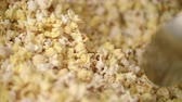 kernels : Worker mixing popcorn in popcorn machine with scoop. Cinema entertainment background. Close up of hand mixing ready popcorn flakes in slow motion. Preparing food for movie theatre