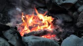 Close up of a hot campfire in a rock ring burning with wind blowing the smoke