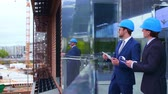 yatırım yapmak : Real estate developers in helmets. New office construction. Confident business men and architect talking in front of modern office building. Businessman and his colleague.
