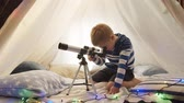 chata : Little boy playing with a telescope in childrens tent at home. Happy caucasian kid in the playroom. Dostupné videozáznamy