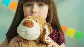 tatarak : Cute little girl kissing her toy teddy bear and showing hiw to the camera. Close up