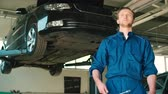 yenilemek : Caucasian young auto mechanic in blue uniform with blue eyes standing at the autoservice and holding a cross wrench in hand. Indoor.