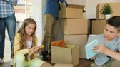carry out : Beatiful caucasian family opening and pulling out things from the box and having fun. Stock Footage