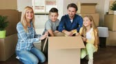 carry out : Portrait of happy family opening big cardboard box, turning to the camera and smiling. Close up shot.
