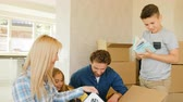 проведение : Close up shot of beatiful happy family opening big cardboard box while they moving to the new house.