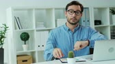 clothe : Young business man in glasses checking final financial report while his work day is finishing. Stock Footage
