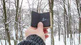 písemný : Frost idea. Hand holding a book with the inscription Brr the background of the forest Dostupné videozáznamy