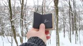 písemný : Winter or cold idea. Hand holding a book with the inscription Brr the background of the forest