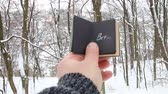 písemný : Winter or cold creative idea. Hand holding a book with the inscription Brr the background of the forest Dostupné videozáznamy
