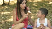 family values : The mother gives the son to lick her ice cream. The mother and son rest in the Park
