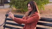 vintage : Young woman takes selfie on mobile phone and smiling. Young woman with new smartphone in Park Stock Footage