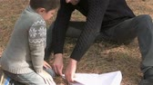 vintage : Fathre and son make paper airplane in forest. Close up. Little boy playing paper airplane with his father in wood Stock Footage