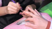 эмаль : Manicurist spreads nails with special varnish. Actual process of performing manicure. Woman in nail salon