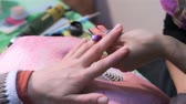 эмаль : Applying bright nail on nails. Close up. Actual process of performing manicure. Woman in nail salon