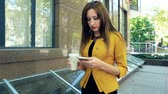 Business woman writing sms on mobile phone and drinking coffee. Business woman walking in business district with cup of coffee