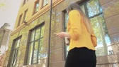 Business woman walking down street with coffee and telephone. View from bottom. Business woman walking in business district with cup of coffee Stock Footage