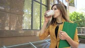 Business lady drinks street coffee during lunch and hurries to office. Business woman walking in business district with cup of coffee