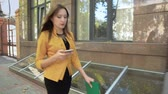 Woman is walking down street along business center and talking on her mobile phone. Business woman with green folder goes to business district Stock Footage