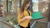 Happy business woman throws over next important documents from folder. Business woman with green folder goes to business district Stock Footage