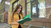 Young woman in yellow jacket throws important paper documents over her head. Business woman with green folder goes to business district Stock Footage