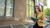 Business lady is angry and throws financial documents out of green folder. Business woman with green folder goes to business district Stock Footage