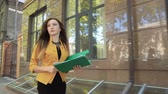 Business lady in yellow jacket is angry and throws financial documents out of green folder. Business woman with green folder goes to business district