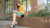 Business lady tears important financial documents and sits near office center. Business woman with green folder goes to business district