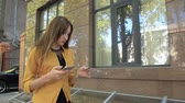 Woman in yellow jacket makes online purchase using phone. Business woman makes purchases on internet Stock Footage