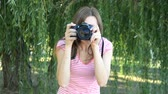 Young woman turtsits with mirror camera on background of trees Stock Footage