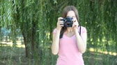 Beautiful woman tourist goes and takes photos using DSLR photo camera Stock Footage
