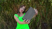 Young woman makes funny selfi using black tablet near thickets of reed