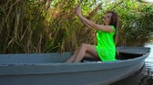 Young woman on boat doing selfie on tablet on wooden boat Stock Footage
