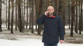 Bald man in glasses talking on mobile phone in winter snowy forest Stock Footage